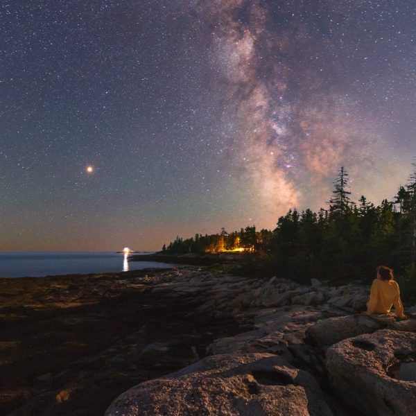 A tourist takes a moment to observe the nightsky and beautiful coastline in Southport, Maine.