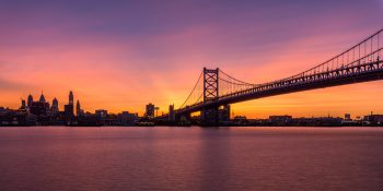 Photograph of the Ben Franklin Bridge and Philadelphia skyline with a brilliant sunset.