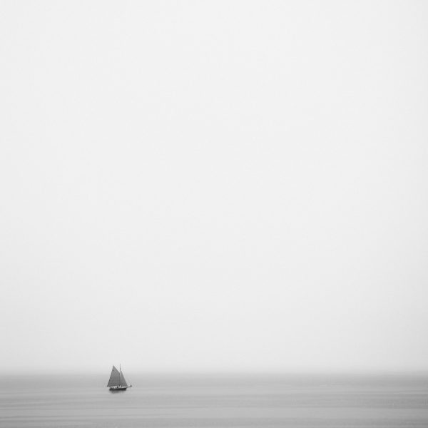 Large photograph of a tiny sailboat on a large ocean expanse with the sky taking up 90% of the photo.